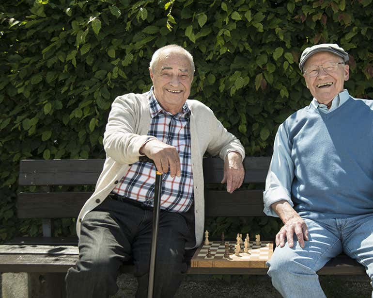 Two senior men play chess in the park, smiling at the camera.