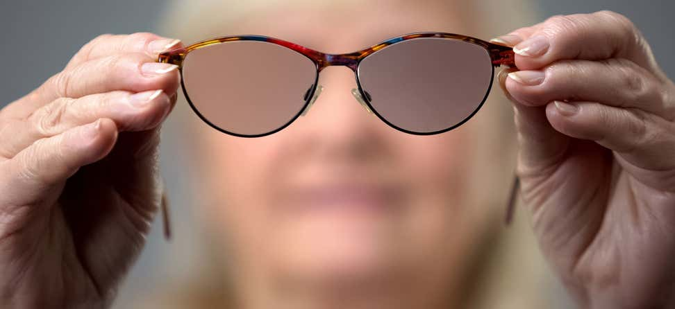 A senior Caucasian woman is holding blurred glasses up close to the camera, indicating the concept of vision loss.