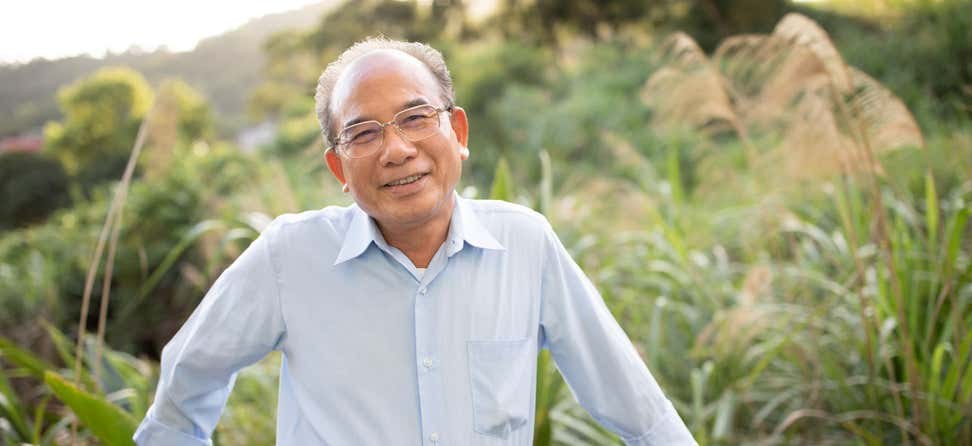 An older Asian man smiles on the balcony of his house.
