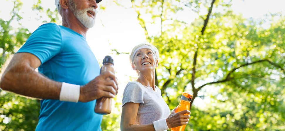 A senior Caucasian couple is out for a run in the park on a sunny day.