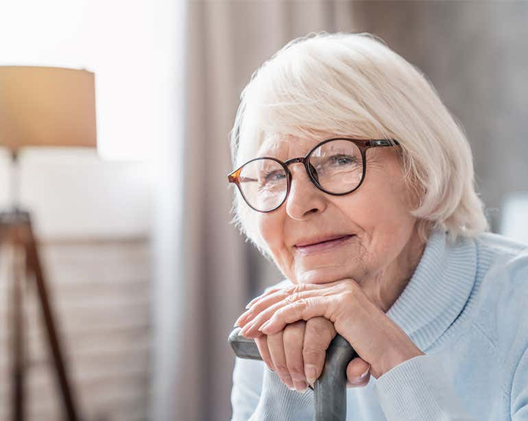 A senior Caucasian woman wearing glasses is smiling, resting her chin on her hands while holding a cane.