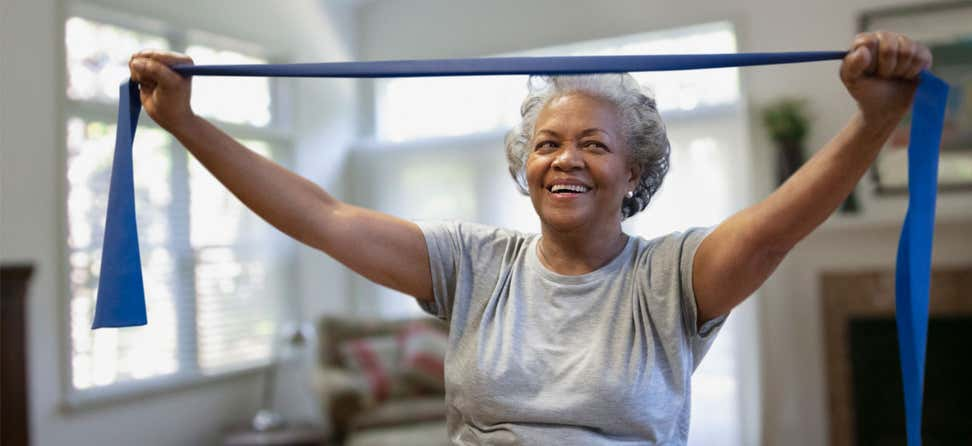 A senior Black woman is doing band exercises in the comfort of her own home.