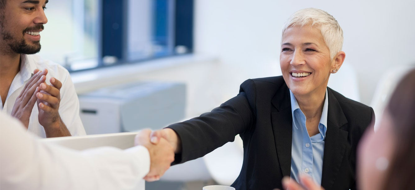 A senior business woman with short hair is smiling while she's shaking hands with another colleague.
