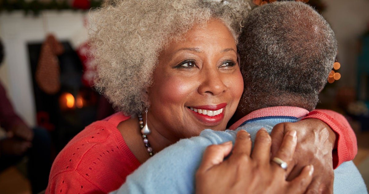 A close up shot of a Black senior woman smiling as she hugs her companion.