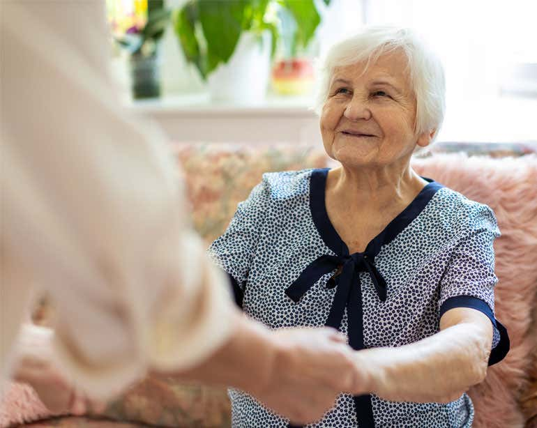 A senior Caucasian woman is receiving help getting up from a seated position from her caregiver.