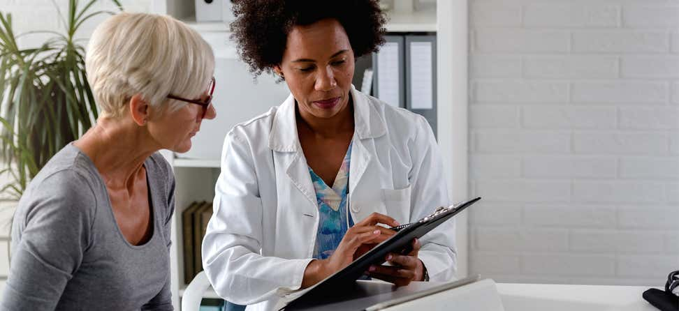 A senior Caucasian woman is listening to her healthcare options from a Black female doctor.