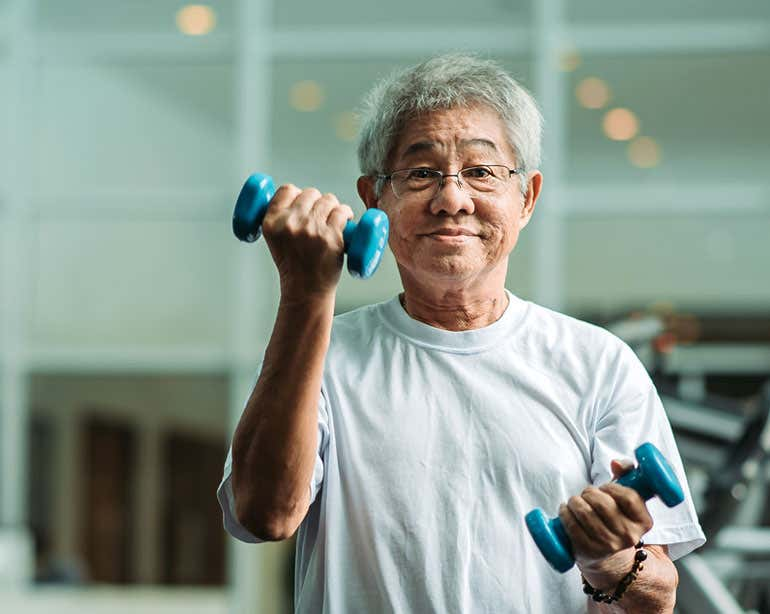 A senior Asian man is seen lifting weights in the gym.