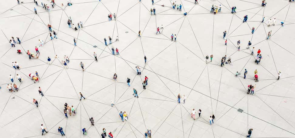 An aerial view of people walking around connected by lines, indicating a network.
