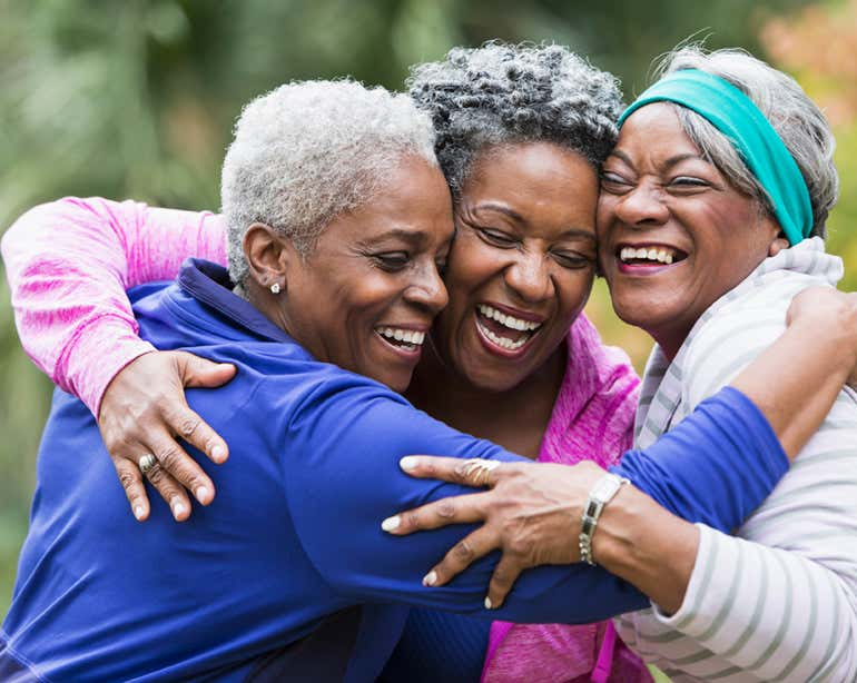 Three senior African American women are at a park hugging.