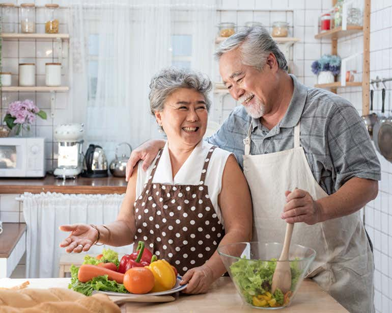 A senior Asian couple is in the kitchen smiling at each other while preparing a healthy meal.
