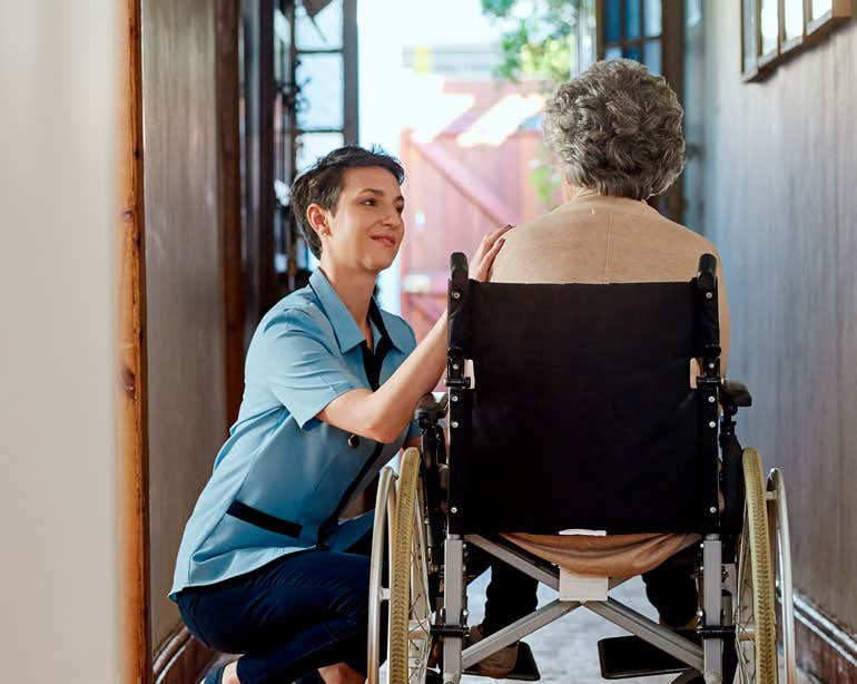 A younger caregiver with short dark hair is caring for a female senior woman in a wheelchair whose back is turned to the camera.