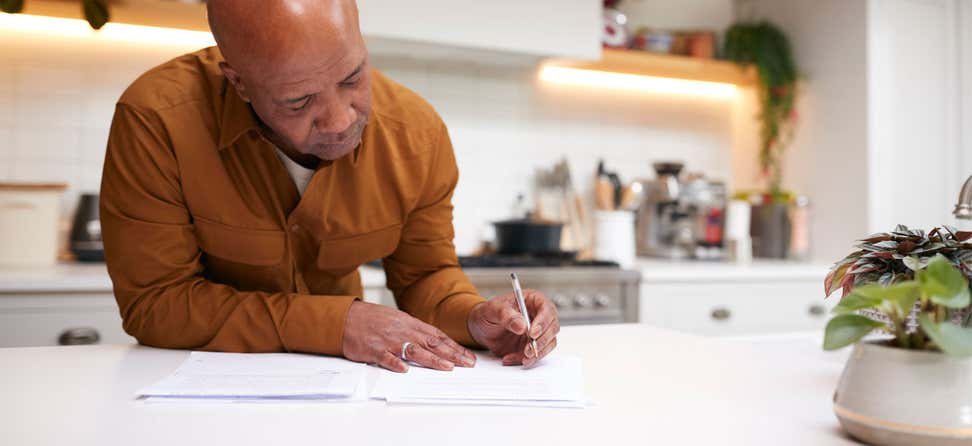 An older black man is reviewing and signing financial paperwork in his kitchen.