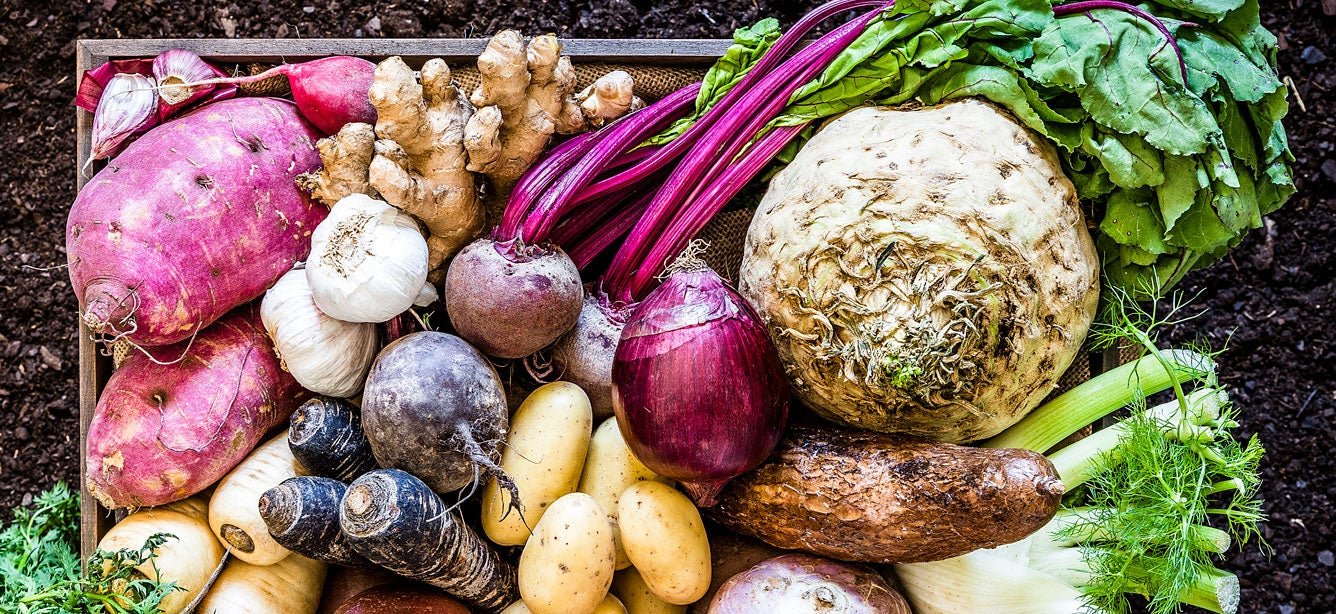 A beautiful artistic shot of a large group of multicolored fresh vegetables in a wooden crate.