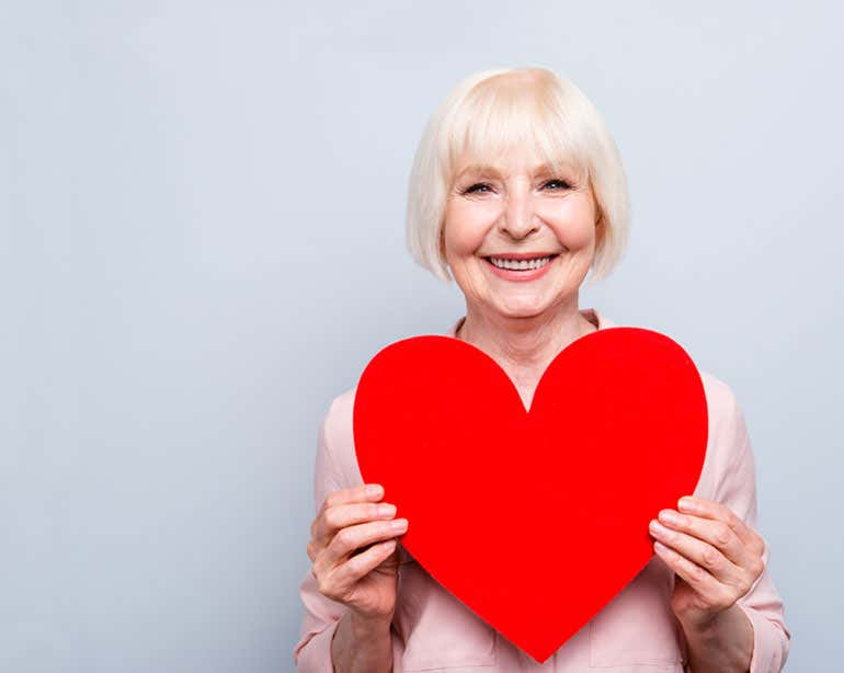 senior white woman holding paper heart