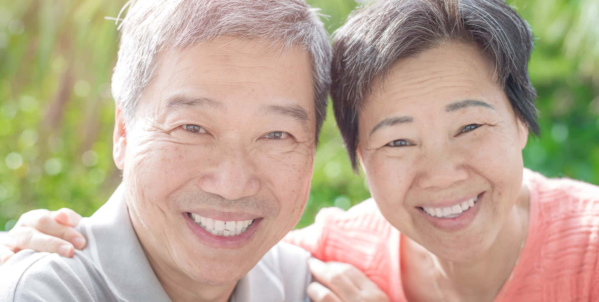 A senior Asian couple is embracing each other, smiling really big for the camera.