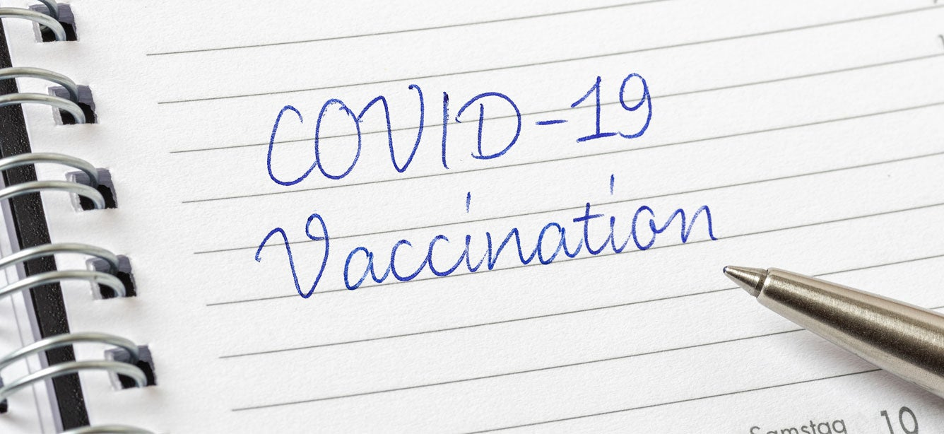 """The words """"COVID-19 Vaccination"""" written in cursive in a day planner with a pen resting on the pad."""