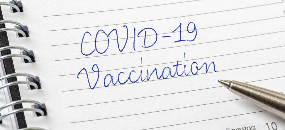 "The words ""COVID-19 Vaccination"" written in cursive in a day planner with a pen resting on the pad."