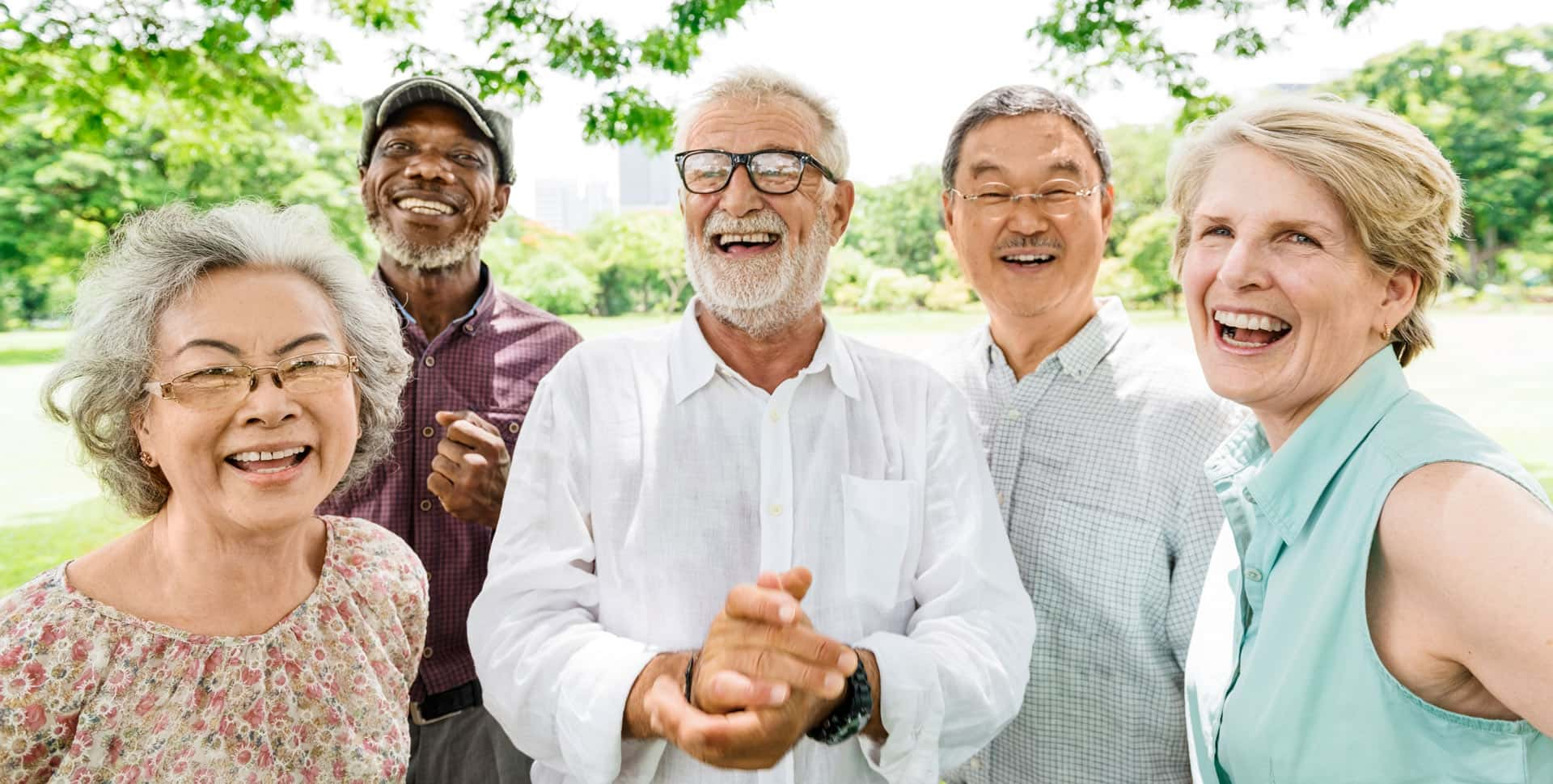 A group of seniors is smiling while outdoors at a park.