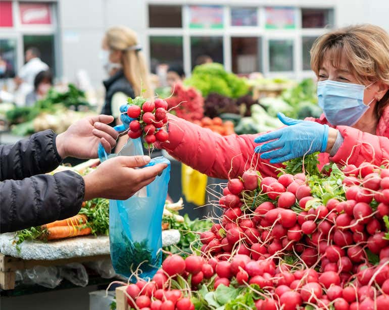 A senior woman is seen shopping for radishes at an outdoor market.