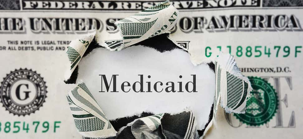 "Image of a U.S. dollar bill ripped in the center with the word ""Medicaid"" showing through."
