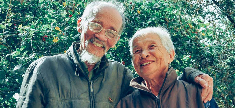 A senior Asian couple walk arm-in-arm outside, smiling and enjoying nature.