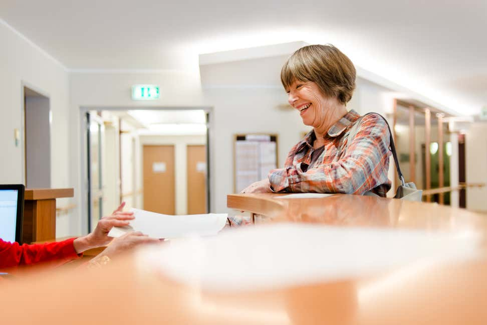 A smiling older woman receives paperwork from someone at a front desk