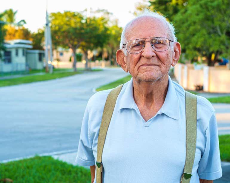 Older man standing on neighborhood street corner