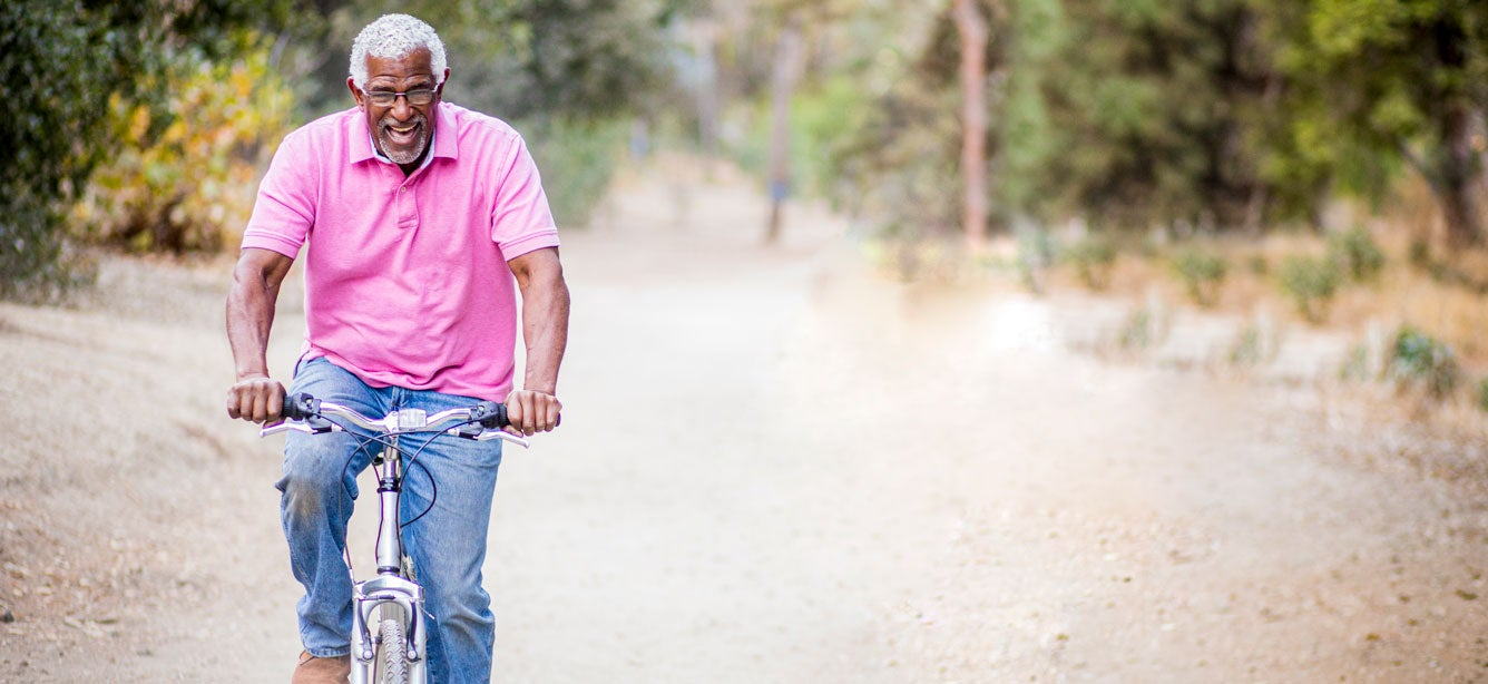 An older black man is riding his bike, laughing and enjoying nature.
