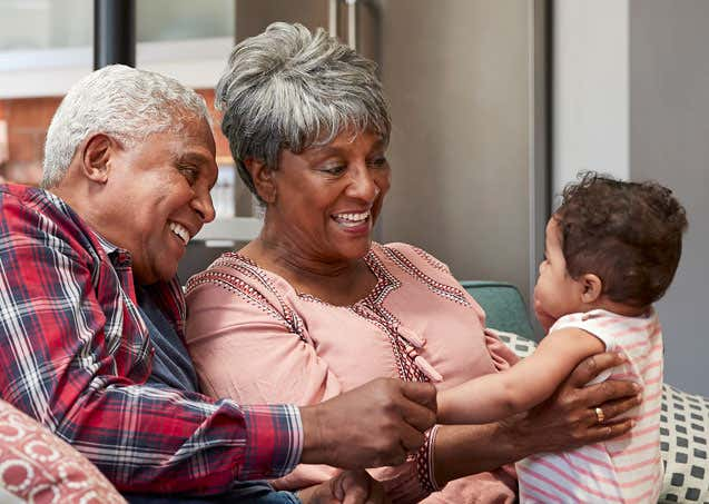 An African American senior couple is sitting on the couch, doting on their grandchild.