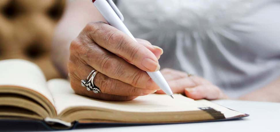 A senior woman is writing on an open notebook during a seminar.