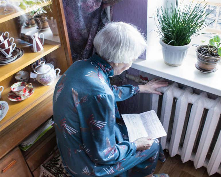 An older woman is seen looking at her utility bill while sitting next to her radiator feeling the warmth.