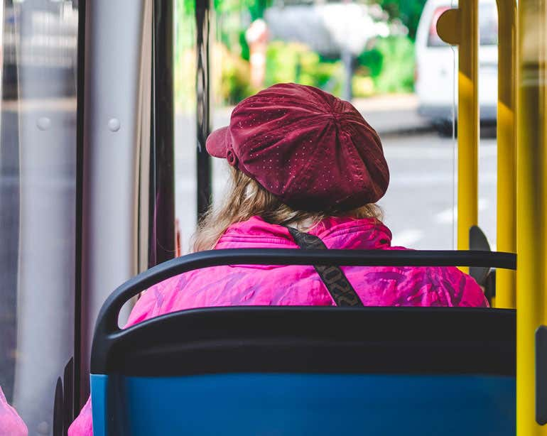 A view from an older woman's back as she sits on a bus.