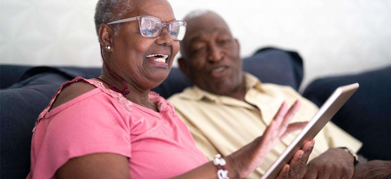 A Black senior woman and her husband are sitting on the couch looking at something on their tablet.