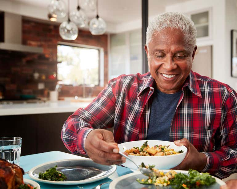 A Black senior man is enjoying a healthy meal at home in his kitchen.