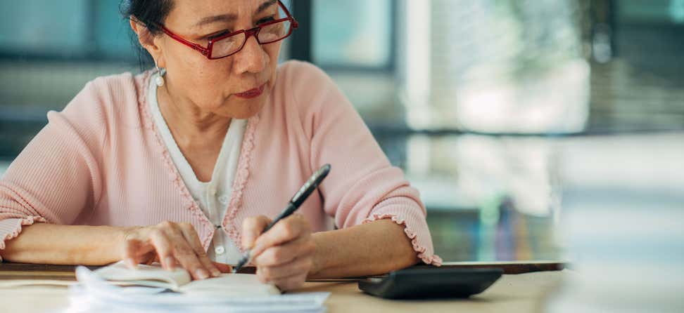 A senior Asian woman is calculating her financials, looking for ways in which she can save in retirement.