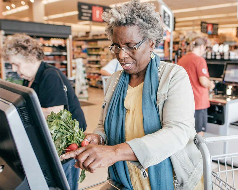 A Black senior woman is seen checking herself out at the grocery store, processing radishes over the payment kiosk.
