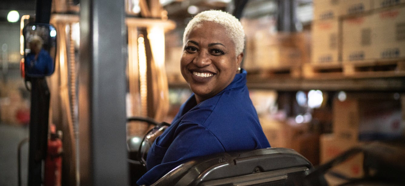 An older, black female is smiling while on the job in a production warehouse.