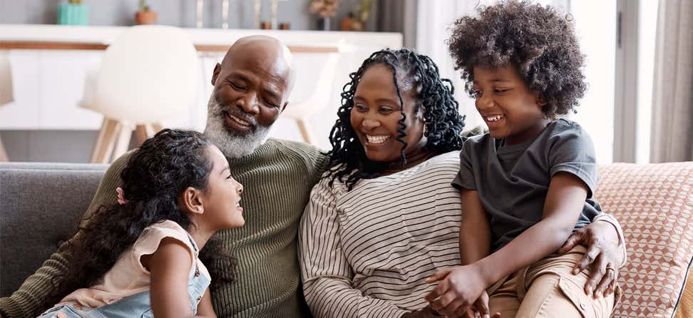 A happy Black, intergenerational family is sitting on the couch at home.