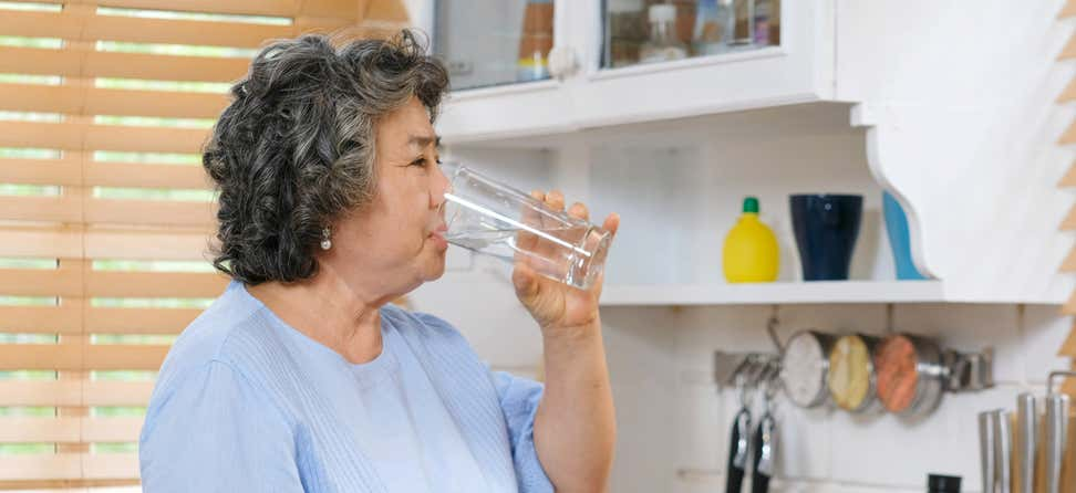 Older Asian woman drinking a glass of water in the kitchen