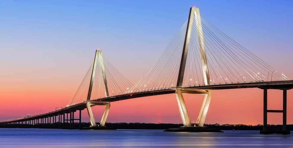 A beautiful shot of the Arthur Ravenel Jr Cooper River Suspension Bridge from shore at sunset.