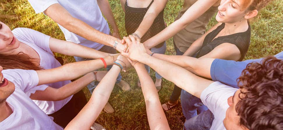 A group of multi-generational people have their hands in a huddle, signifying teamwork.