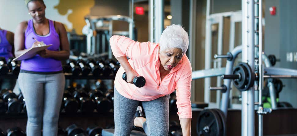 A senior Black woman is lifting weights in the gym with her trainer.