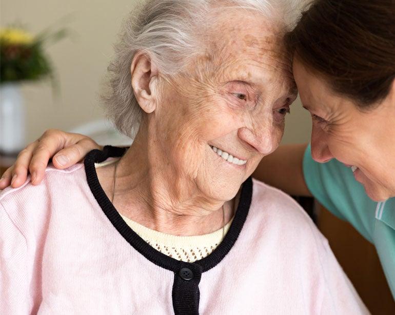 A senior woman smiles, hugging her caregiver during her house visit.