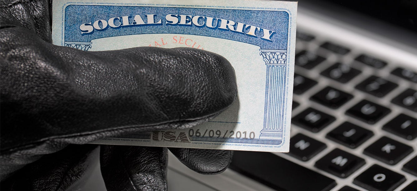 A thief with a black glove on holds a social security card while trying to access a stolen computer.