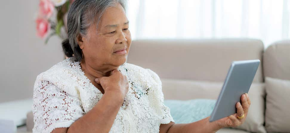 An Asian senior woman is holding her tablet up, making a decision about her health.