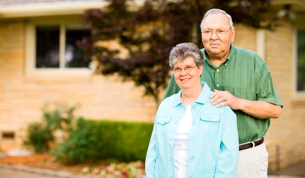 Senior couple standing outside their house