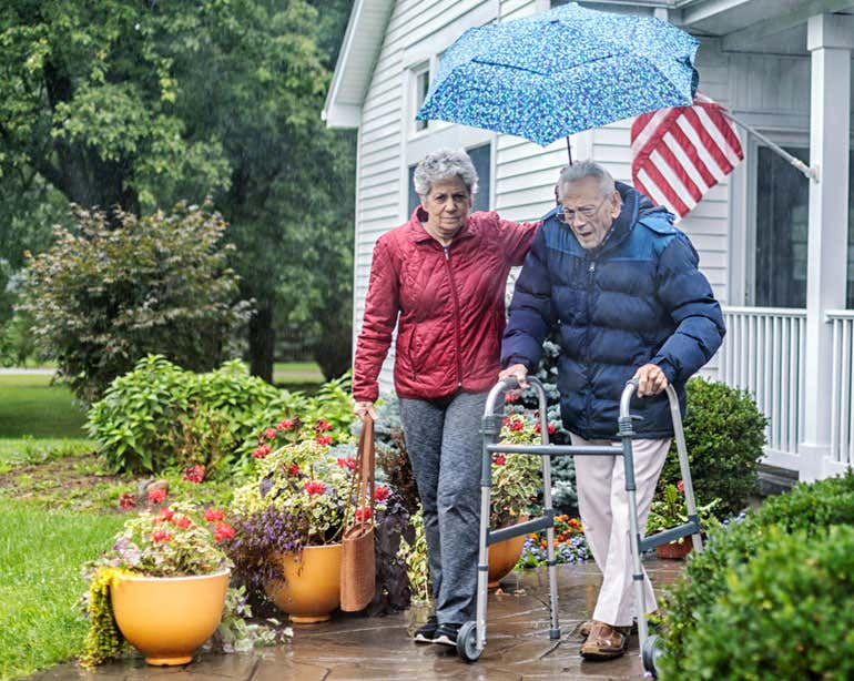 An older female caregiver helps a male veteran who's walking out of his home with a walker.