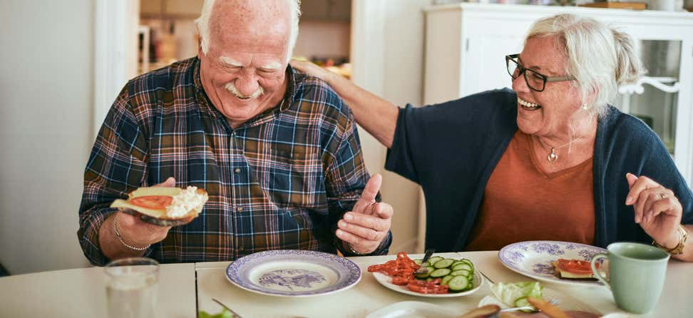 A senior couple is laughing at the dinner table while eating a healthy meal together.