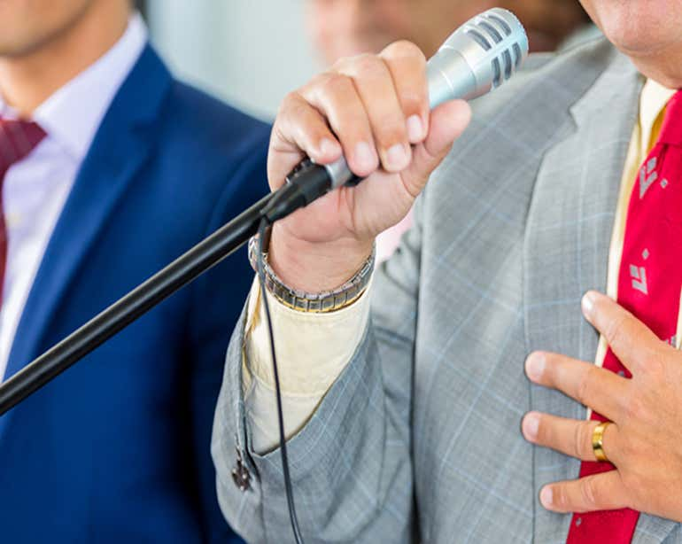 Close up shot of a public citizen speaking into the microphone at a public townhall.