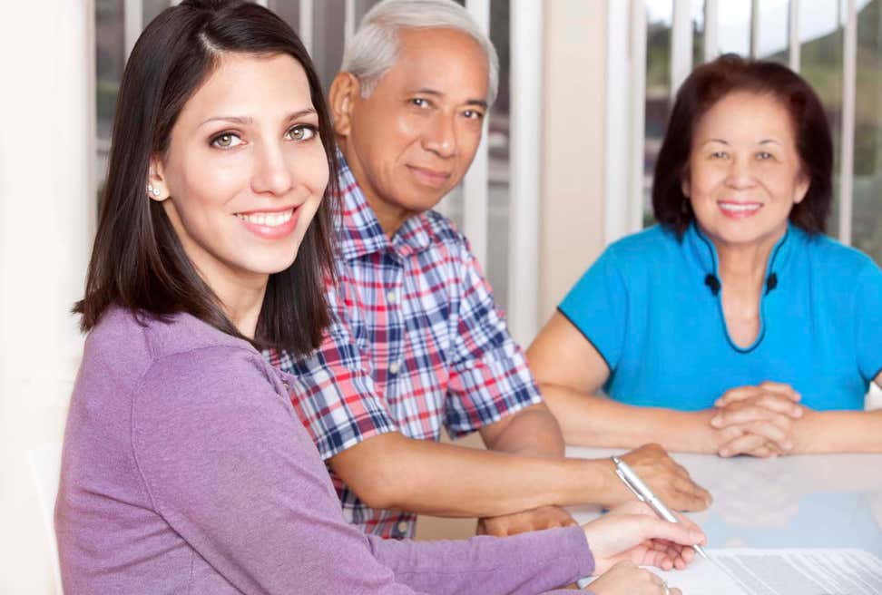 Counselor with older Asian couple at table filling out paperwork.
